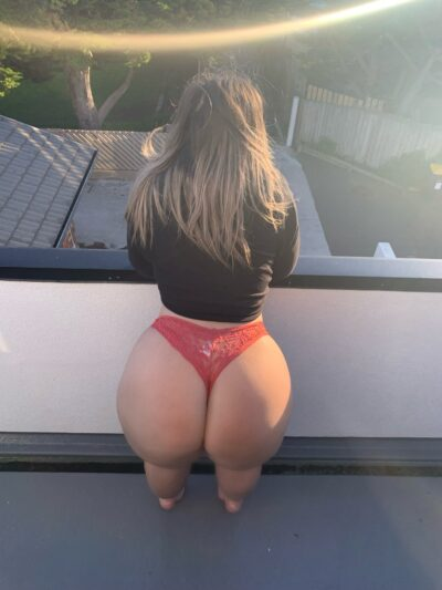 Olivia standing with back to camera on a balcony, leaning on elbows on rail. Olivia wears a black long sleeve top, red panties and has long light brown hair. NZ Pleasures.