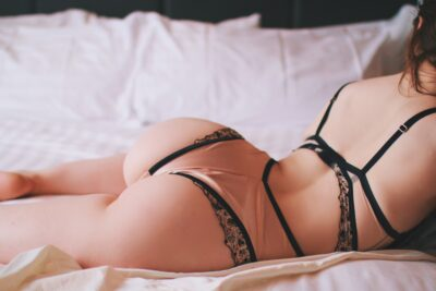 Tilly Watts lying on her front across a bed of white, one knee bent up, leaning up on elbows, side on to camera. Tilly wears a beige and black bodysuit and has long auburn hair. NZ Pleasures.