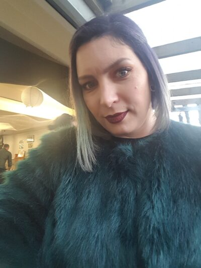 Portrait photo of Delilah looking at the camera, head titled to one side. Delilah wears a green fax fur long sleeve top and has shoulder length multicoloured hair. NZ Pleasures.